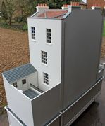 Bespoke Regency dolls house view of back with detachable courtyard and outbuildings.