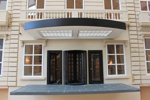 Bespoke grand 1920s dolls house hotel entrance canopy with revolving door.