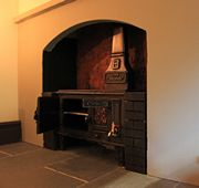 Regency dolls house kitchen with closed Helmer range in one of the inglenook arches.