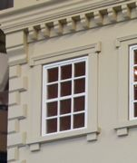Regency dolls house with handmade first floor windows, balcony and additional architectural details surrounding windows.