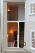 Regency dolls house: Kensington House with top panel opened, showing first floor landing and cupboard stairs.